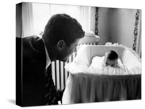 Sen. John F. Kennedy Playing Peek-A-Boo with His Daughter Caroline in Her Crib by Ed Clark