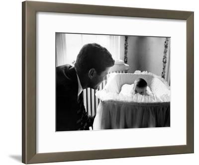 Sen. John F. Kennedy Playing Peek-A-Boo with His Daughter Caroline in Her Crib