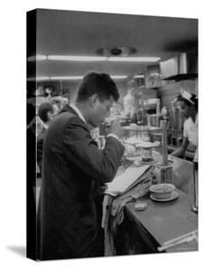 Senator John F. Kennedy Drinking a Cup of Coffee at a Cafe in Washington Airport by Ed Clark