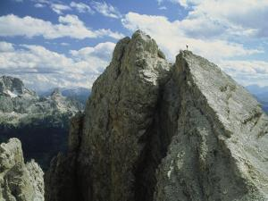 A Climber Standing at the Top of a Mountain in the Dolomites, Italy by Ed George