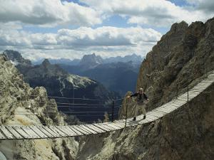 A Man Walking Across a Bridge in the Dolemites, Cortina, Italy by Ed George