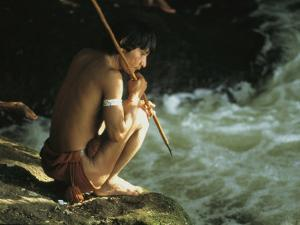 A Pinare Indian Sits by a Stream Fishing by Ed George