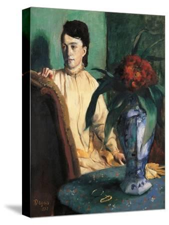 Woman Seated beside a Vase of Flowers
