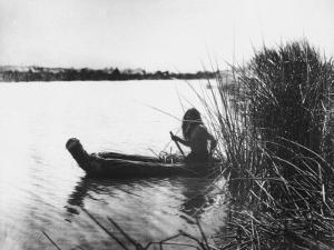 Pomo Indian Poling His Boat Made of Tule Rushes Through Shallows of Clear Lake, Northen California by Edward S^ Curtis