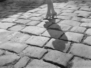 A Lady in High Heels Walks Along a Cobblestoned Street by Edwin L. Wisherd