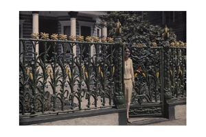 A Woman Stands Next to a Metal Fence Designed after Stalks of Corn by Edwin L. Wisherd
