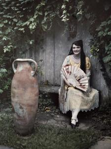 Young Lady Sits on a Bench by a Vase in a French Quarter Garden by Edwin L. Wisherd