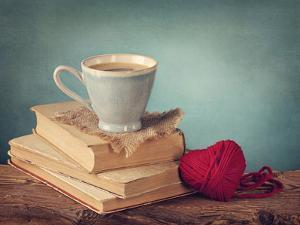 Cup of Coffee Standing on Old Books and Wool Heart by egal