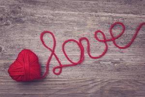 Red Heart of Red Wool Yarn on a Wooden Background by egal