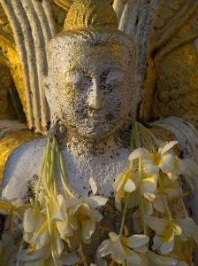 Close up of Small Buddha Figure with Flowers Round the Neck in the Shwedagon Paya, Yangon, Myanmar by Eitan Simanor