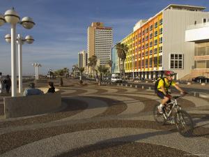 Cyclist on Jerusalem Beach Promenade with Dan Hotel Facade Decorated by Yaaqov Agam in Background by Eitan Simanor