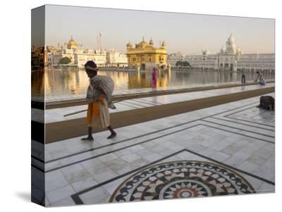 Elderly Sikh Pilgrim with Bundle and Stick Walking Around Holy Pool, Amritsar, India