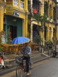 Man Riding a Bike and Holding Umbrella, Hoi An, Indochina by Eitan Simanor