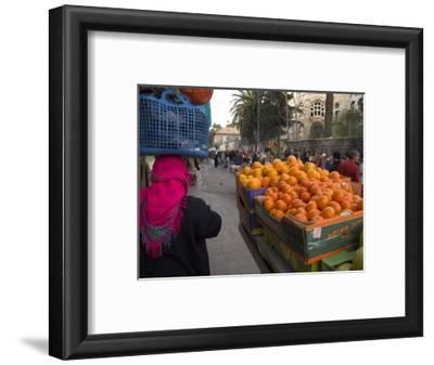 Palestinian Woman in Colourful Scarf and Carrying Bag on Her Head Walking Past an Orange Stall