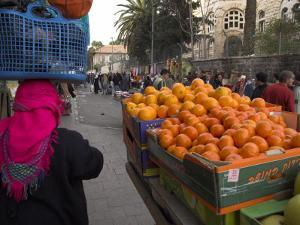 Palestinian Woman in Colourful Scarf and Carrying Bag on Her Head Walking Past an Orange Stall by Eitan Simanor