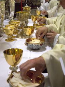 Priests' Hands Taking the Host During Mass in Easter Week by Eitan Simanor