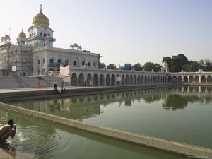 Sikh Pilgrim Bathing in the Pool of the Gurudwara Bangla Sahib Temple, Delhi, India by Eitan Simanor