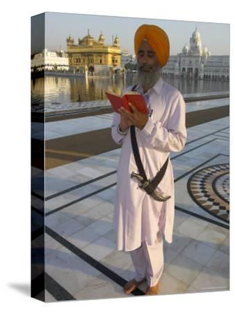 Sikh Pilgrim with Orange Turban, White Dress and Dagger, Reading Prayer Book, Amritsar