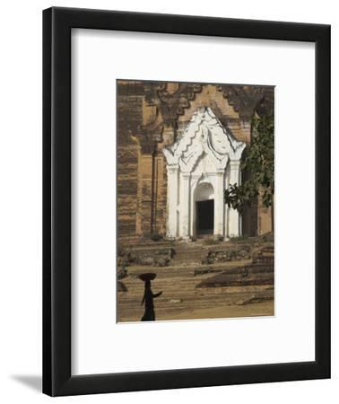 Silhouette of a Woman with Tray on Her Head Walking Past Stupa Entrance, Near Mandalay, Myanmar
