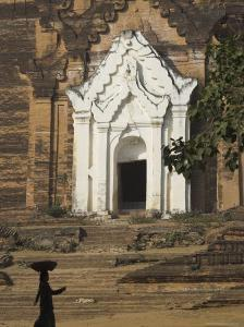 Silhouette of a Woman with Tray on Her Head Walking Past Stupa Entrance, Near Mandalay, Myanmar by Eitan Simanor