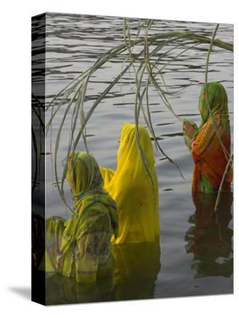 Three Women Pilgrims in Saris Making Puja Celebration in the Pichola Lake at Sunset, Udaipur, India