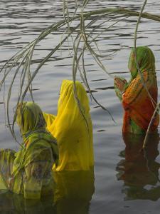 Three Women Pilgrims in Saris Making Puja Celebration in the Pichola Lake at Sunset, Udaipur, India by Eitan Simanor