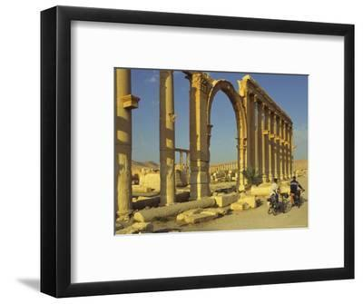 Two Cyclists Pass the Great Colonnade (Cardo), Palmyra, Unesco World Heritage Site, Syria