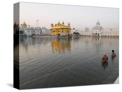 Two Sikh Pilgrims Bathing and Praying in the Early Morning in Holy Pool, Amritsar, India