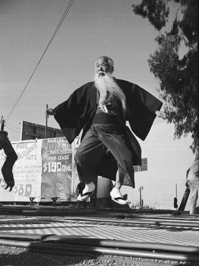 Elderly Japanese Movie Extra Jumping on Trampoline-Ralph Crane-Photographic Print