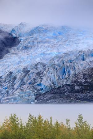 Bright blue ice of Mendenhall Glacier flowing from Juneau Ice Field, mist on Mendenhall Lake, Junea