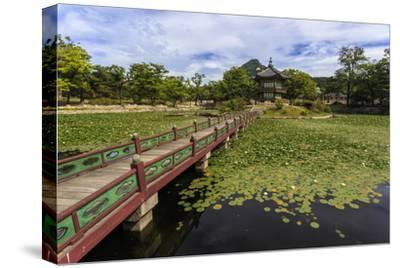 Hyangwonjeong Pavilion and Chwihyanggyo Bridge over Water Lily Filled Lake in Summer, South Korea