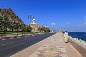 Man Wearing Dishdasha Walks Along Mutrah Corniche with National Flags, Middle East by Eleanor Scriven