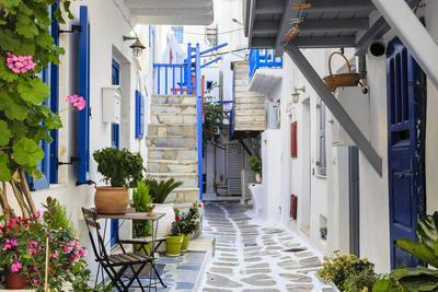 Narrow street, whitewashed buildings with blue paint work, flowers, Mykonos Town (Chora), Mykonos,