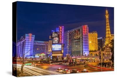 Neon Lights on Las Vegas Strip at Dusk with Car Headlights Leaving Streaks of Light