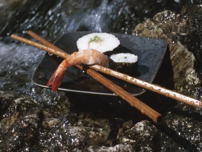 Elegant Sushi and Chopsticks Beside Rushing Water--Photographic Print