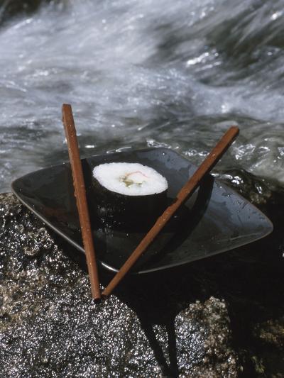 Elegant Sushi and Chopsticks Beside Rushing Water--Photographic Print