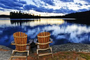 Landscape with Adirondack Chairs on Shore of Relaxing Lake at Sunset in Algonquin Park, Canada by elenathewise