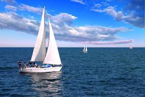 Sailboat Sailing in the Morning with Blue Cloudy Sky by elenathewise