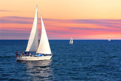 Sailboat Sailing towards Sunset on a Calm Evening