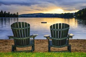 Two Wooden Chairs on Beach of Relaxing Lake at Sunset. Algonquin Provincial Park, Canada. by elenathewise