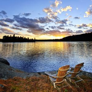 Wooden Chair on Beach of Relaxing Lake at Sunset in Algonquin Park, Canada by elenathewise