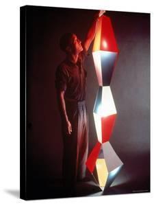 Japanese American Sculptor Isamu Noguchi Adjusting a Light Sculpture He Designed by Eliot Elisofon