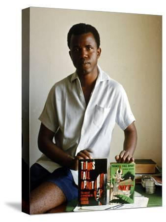 Nigerian Author Chinua Achebe Holding Two Editions of His Book Things Fall Apart