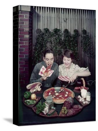 Teen Couple Eating Pizza from a Garden Table, 1960