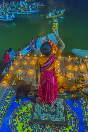 India, Varanasi Young Boy in Pink and Yellow Robes Holds Up an Offering to the Ganges River