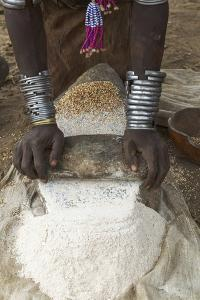 Africa, Ethiopia, Southern Omo, Karo Tribe. Woman grinding grain into flour with stone. by Ellen Goff