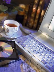Laptop Computer, Cd-Rom, Cup of Tea, and Books by Ellen Kamp