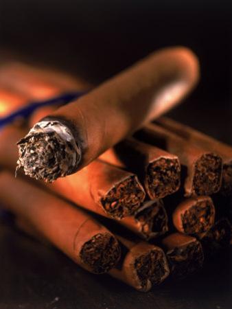 Lit Cigar on Top of Bundle of Cigars