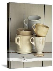 Various Light Coloured Cups on Wooden Shelf by Ellen Silverman