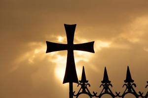 A wrought-iron cross on a fence in Syria at sunrise. by Emily Wilson